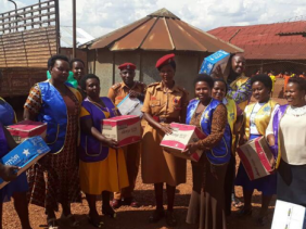 Chrispine Musimenta Rwaboona (on the left of the Police woman) delivering donations to inmates at Ndorwa Prison in Kabale